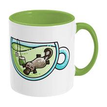 Load image into Gallery viewer, Cute platypus swimming in a glass teacup of green tea design on a two toned green and white ceramic mug, showing RHS