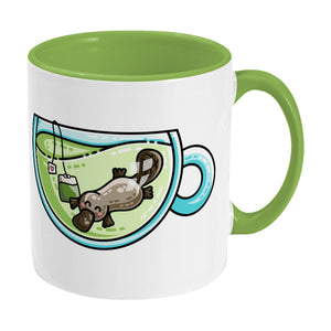 Cute platypus swimming in a glass teacup of green tea design on a two toned green and white ceramic mug, showing RHS