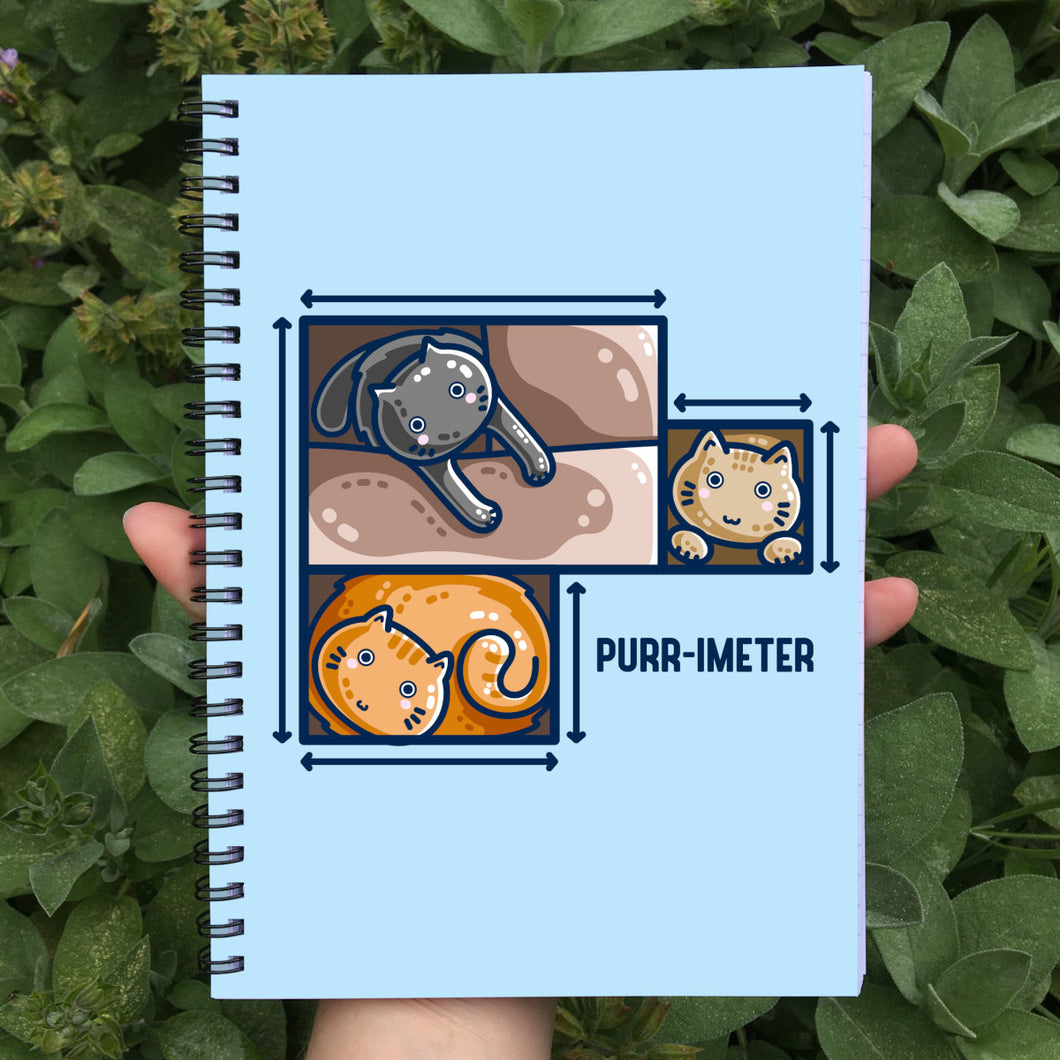 A pale blue spiral notebook held in a hand showing the front cover which features three cute cats in adjoining cardboard boxes seen from directly above, with measurement lines around the edges and the word 'purr-imeter'.