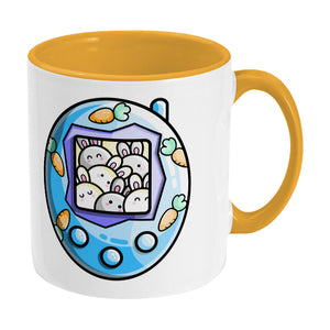 Cute blue rabbit and carrots tamagotchi design on a two toned yellow and white ceramic mug, showing RHS