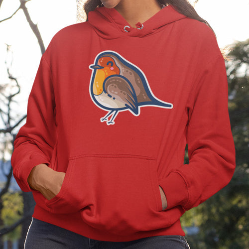 Torso of a woman wearing a red unisex hoodie with her hands in the front pouch and the neck cords tucked in featuring a design on the chest of a kawaii cute robin bird facing to the left with a white border surrounding it