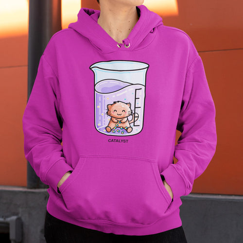 The torso of a woman wearing a hot pink colour hoodie with her hands in the front pouch and the neck cords tucked away with a design on the chest of a chemistry beaker of purple liquid with a ginger cat sitting in it joining atoms into molecules and the word catalyst written beneath in black capitals