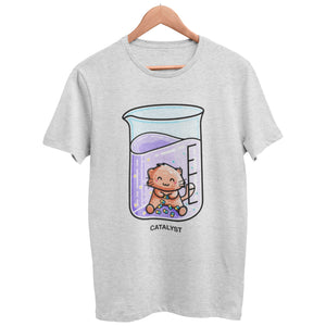 A heather grey unisex crewneck t-shirt on a hanger with a design on its chest of a cute ginger cat sitting in a chemistry beaker of purple liquid joining atoms or yellow and green together
