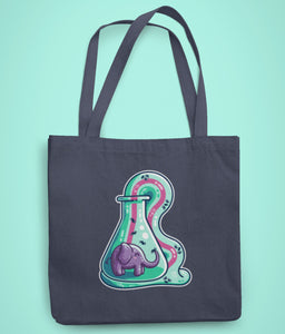 A dark blue coloured fabric tote bag lying flat against a pale turquoise background with a design in the center of a conicle flask with a purple elephant inside and green foam coming out and down with a pink stripe along the middle of it with small molecules represented in the foam.