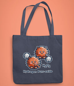 A dark blue coloured fabric tote bag lying flat against an orange background with a design in the center of a hydrogen peroxide molecule represented as circular white and ginger cats with the words H202 hydrogen purr-oxide.