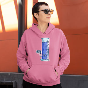 A woman with short hair and sunglasses wearing a candyfloss pink colour hoodie with her hands in the front pouch and the neck cords tucked in with a design on the chest of a kawaii cute enthusiastic graduated cylinder of blue liquid with a blue speech bubble saying be a litre