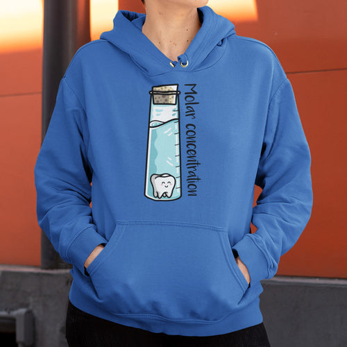 Torso of a woman wearing a royal blue colour hoodie with her hands in the front pouch and neck cords tucked away with a design on the chest of a tall corked glass vessel of liquid with a kawaii cute molar tooth in it and the words molar concentration running along the length of the glass vessel written in black