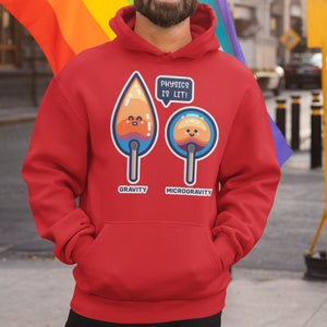 Torso of a bearded man wearing a red hoodie with his hands in the front pouch and the neck cords tucked in with a design on the chest of two kawaii cute matches in flame, one pointed with the word gravity beneath and one circular with the word microgravity beneath and a speech bubble between them saying physics is lit!