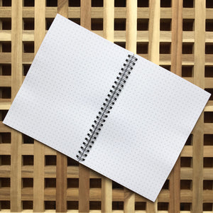 Spiral bound notebook lying open and flat showing pages of grid graph paper like little crosses all over the white paper