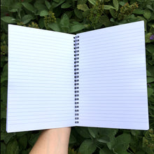 Load image into Gallery viewer, An open notebook held in a hand showing what the lined pages option looks like. Lined white paper and spiral binding.