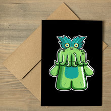 Load image into Gallery viewer, A black greeting card lying flat on a brown envelope, with a design of the StarKid tickle-me-wiggly green plush toy