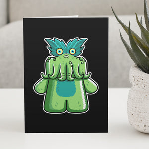 A black greeting card standing on a white table, with a design of the StarKid tickle-me-wiggly green plush toy