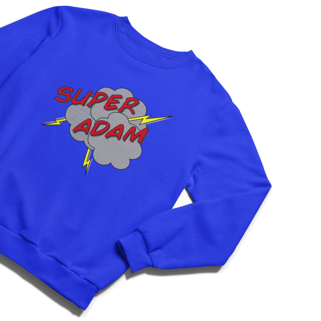 A bright royal blue crewneck sweatshirt with shadowed red lettering saying SUPER ADAM in capital letters with grey half toned clouds beneath and some bolts of lightning protruding from them