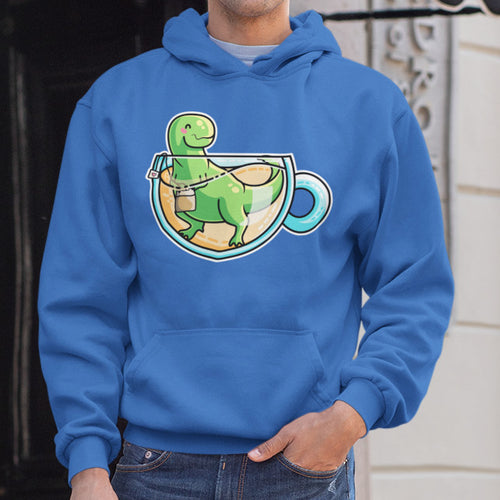 The torso of a man with one hand in his jeans pocket wearing a royal blue hoodie with neck cords tucked in and front pouch and the design of a cup of tea with a green tyrannosaurus rex dinosaur in it