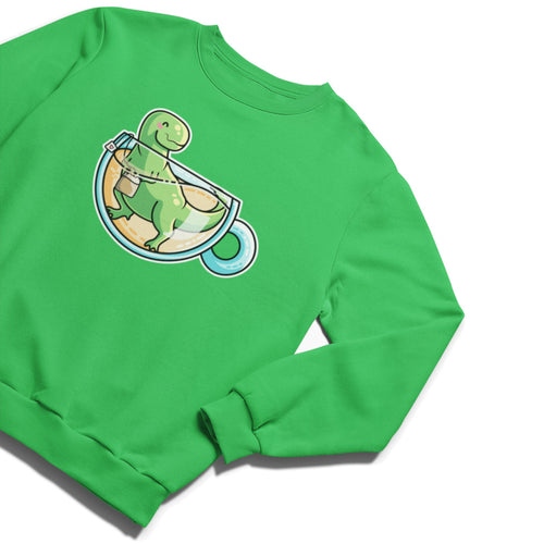 A kelly green unisex crewneck sweatshirt laid flat with a design on the chest of a green tyrannosaurus rex dinosaur standing holding a tea bag in a glass cup of tea