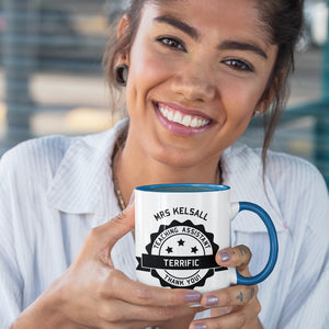 woman holding a personalised black circular banner design with the words 'terrific teaching assistant' on a two toned blue and white ceramic mug