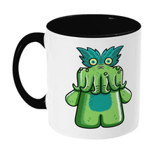 Load image into Gallery viewer, Green tickle-me-wiggly plush toy design on a two toned black and white ceramic mug, showing LHS