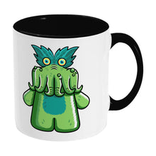 Load image into Gallery viewer, Green tickle-me-wiggly plush toy design on a two toned black and white ceramic mug, showing RHS