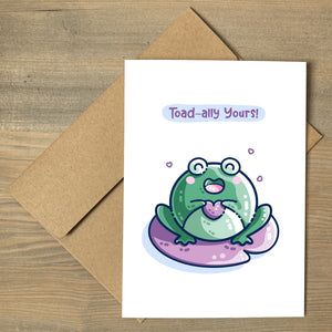 A white greeting card lying flat on a brown envelope and featuring a kawaii cute green toad holding a purple heart and sitting on a purple lilly pad. The words toad-ally yours appear above the toad.