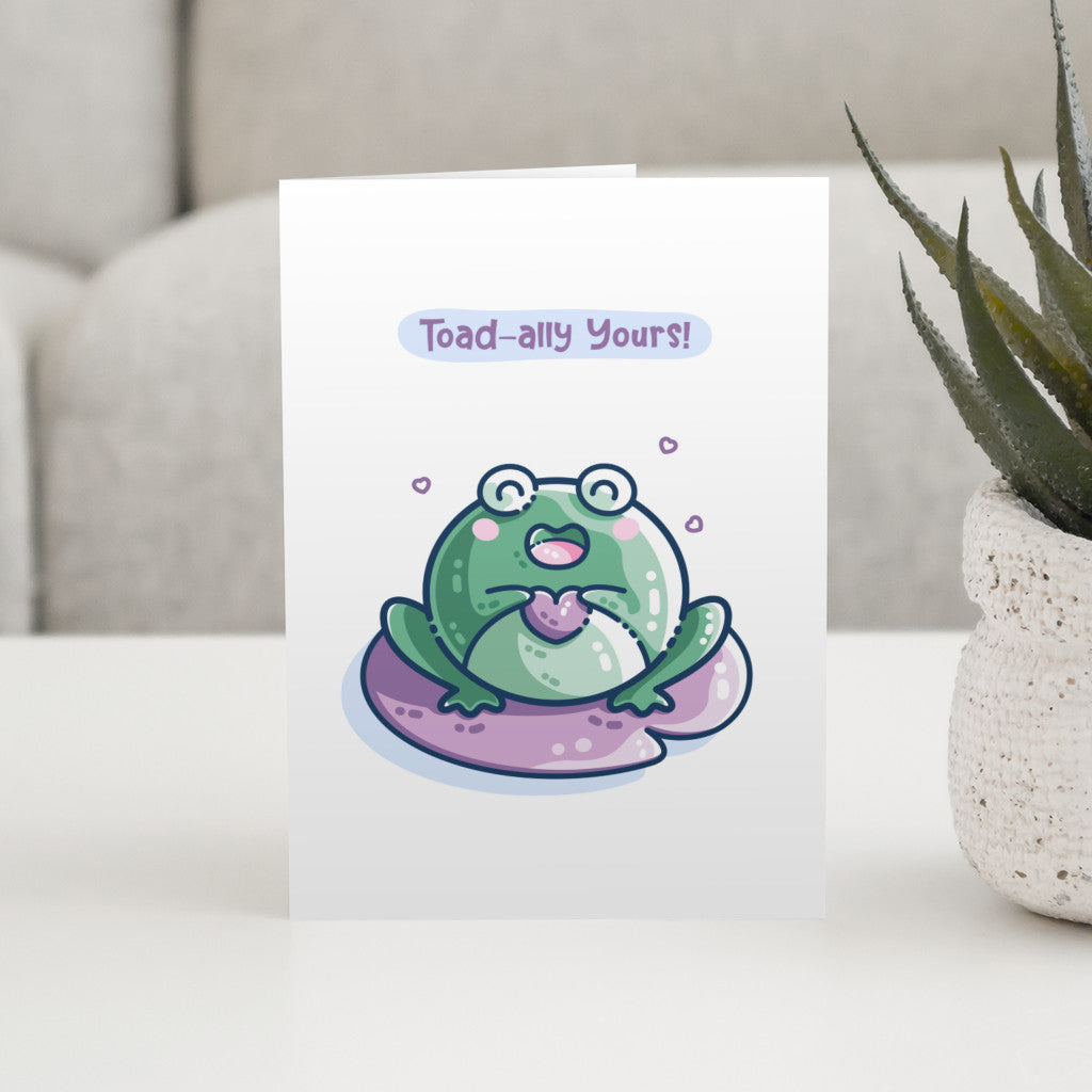 A white greeting card standing on a table and featuring a kawaii cute green toad holding a purple heart and sitting on a purple lilly pad. The words toad-ally yours appear above the toad.