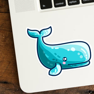a cute turquoise sperm whale shaped vinyl sticker shown stuck on the bottom left hand corner of a laptop computer keyboard