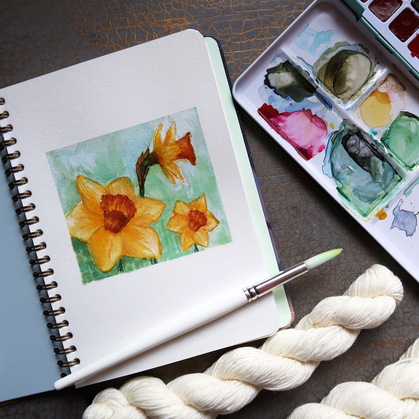 Woollen Wytch February sub club box - yarn subscription box theme reveal - watercolour painted daffodils on a pale blue green background
