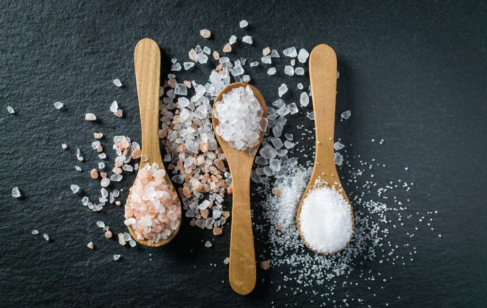 Sea, himalayan and kitchen salt in wooden spoons
