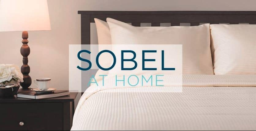 Sobel at Home logo over a hotel bed made up with Sobel Westex pillows and bedding