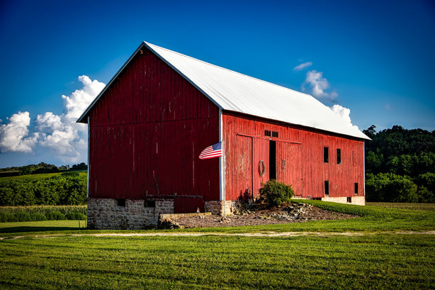 "Red barn in Iowa with American flag, symbolizing ""made in the USA."""