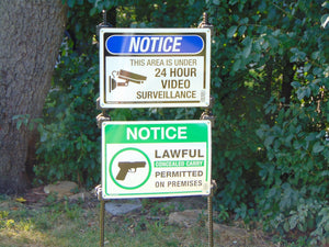 Ez Step-In Posts holding 24 hour video surveillance sign and lawful concealed carry