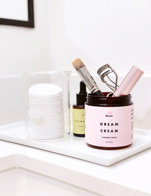 picture of a Deew Dream Cream product filled with makeup brushes on a white bathroom counter top.