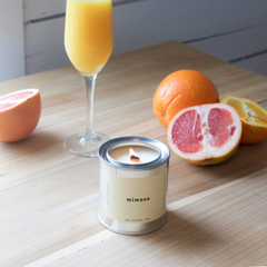 mimosa glass in the background with fresh grapefruit. tin candle in the foreground with label that says mimosa.