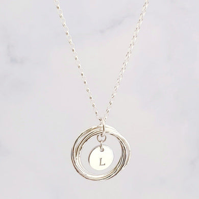Sterling silver rings linked together to form one circle with a personalised disc charm in the centre.