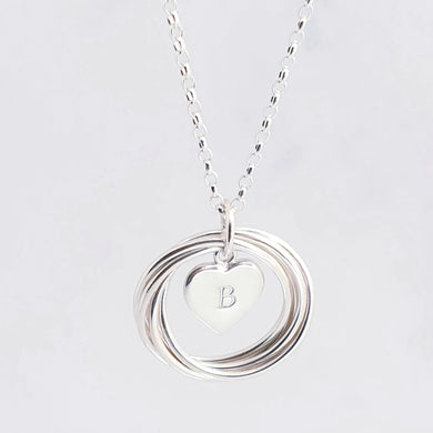 Sterling silver necklace with textured circles, linked to form one circle, with a personalised heart charm in the centre.