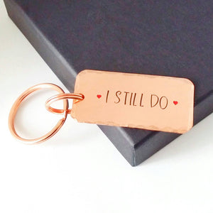 Copper keyring, hand stamped I STILL DO, with red hearts. 40mm x 20mm, textured around the edges. Large and small split rings.