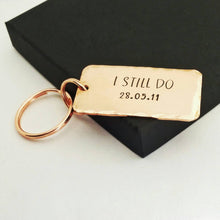 Load image into Gallery viewer, Personalised copper keyring, hand stamped I STILL DO, with the option to add your anniversary date.  Keyring is 45mm x 25mm, textured around the edges and comes with small and large copper finish split rings.