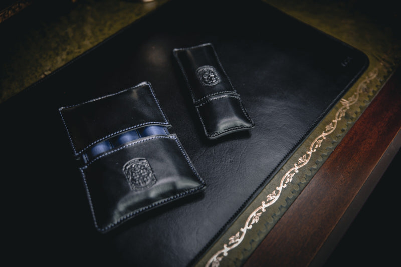 holmes triple leather cigar case closed with coupland crest next to leather double pen holder