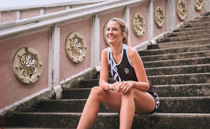 Woman wearing duo motion singlet and shorts on stairs