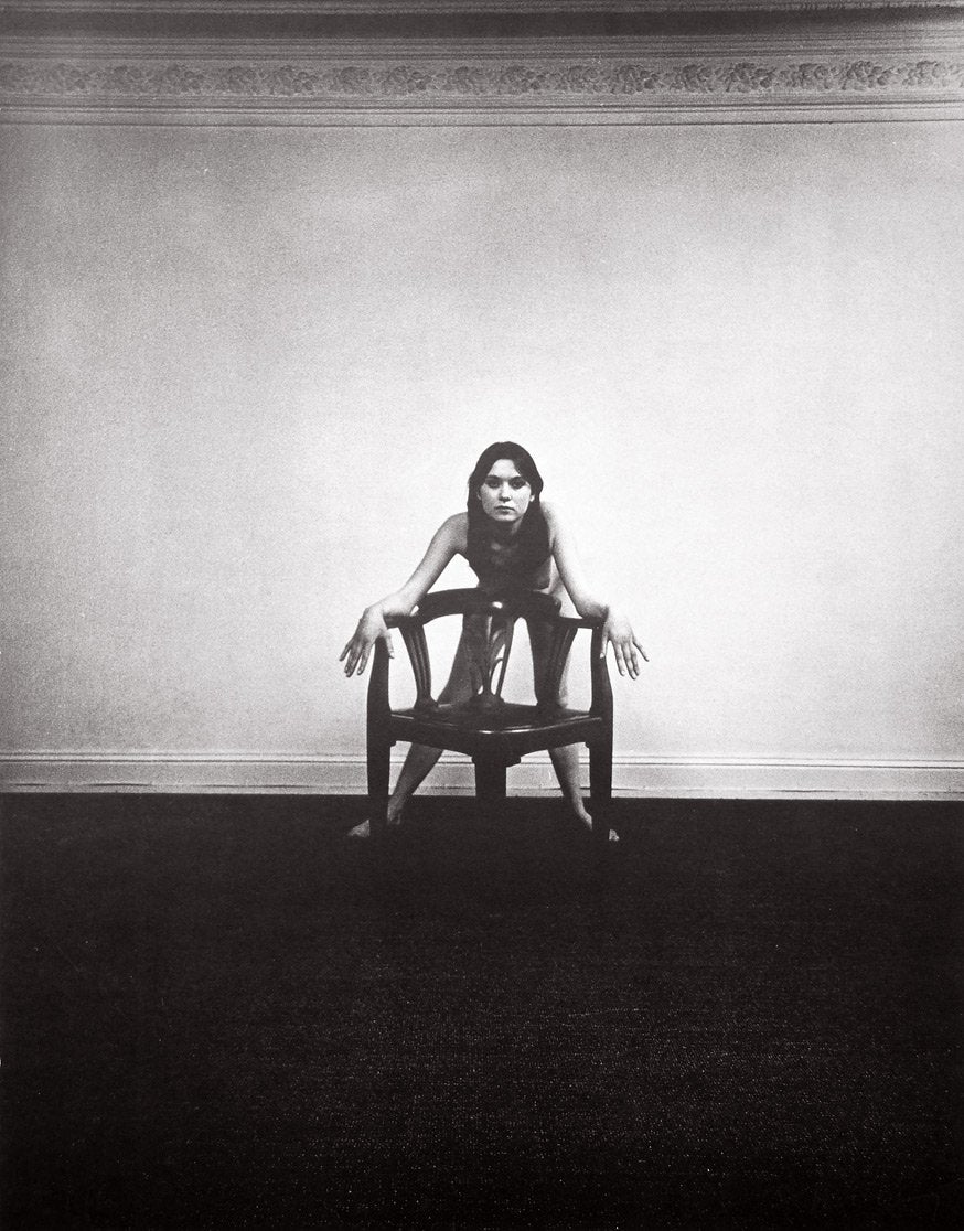 Black and white image of a nude woman leaning on a chair, facing the camera straight on