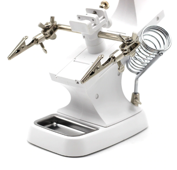 This photo shows the white soldering stand with chrom alligator clamps, solder tool holder, tray in the base of the stand  and adjustable bar. It is a closer of up view of these features.