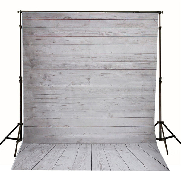 Photo showing photo backdrop hanging from backdrop stand. Backdrop is of grey weathered wood boards. The portion of the backdrop that is in on the floor shows boards running in the same direction as the viewer. The boards on the vertical portion of the backdrop are 90 degrees to the floor boards.