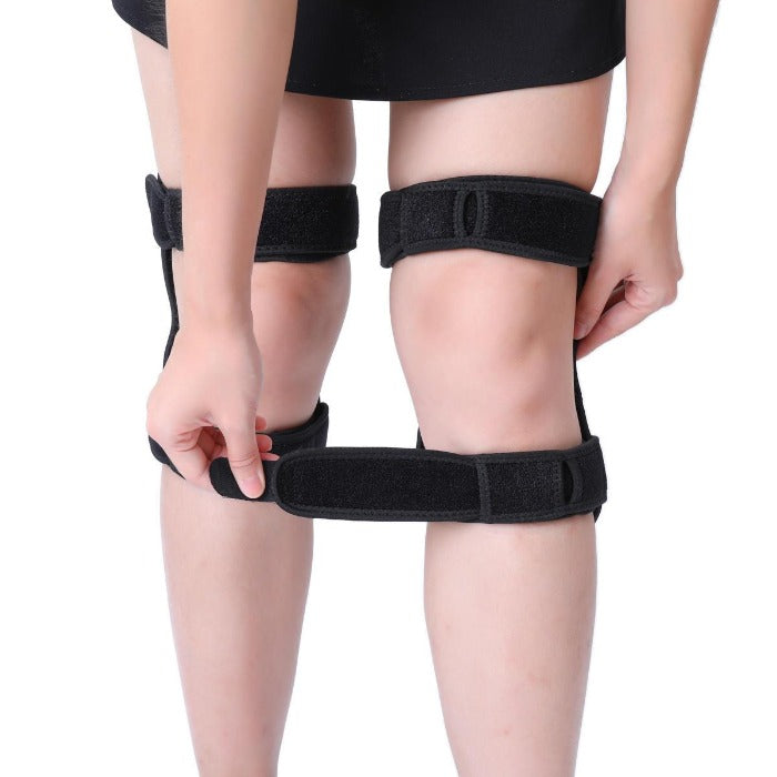 Photo of person in black skirt or short pants putting on the showing Knee Brace Support With Spring Hinge by attaching the hook closure straps . One hand is holding the showing Knee Brace Support With Spring Hinge close the leg while the other is tightening the hook closure strap so the showing Knee Brace Support With Spring Hinge will stay on the leg when moved.