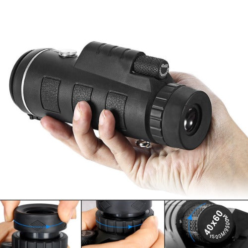 Hand holding monocular lens. View adjustment dials also shown.