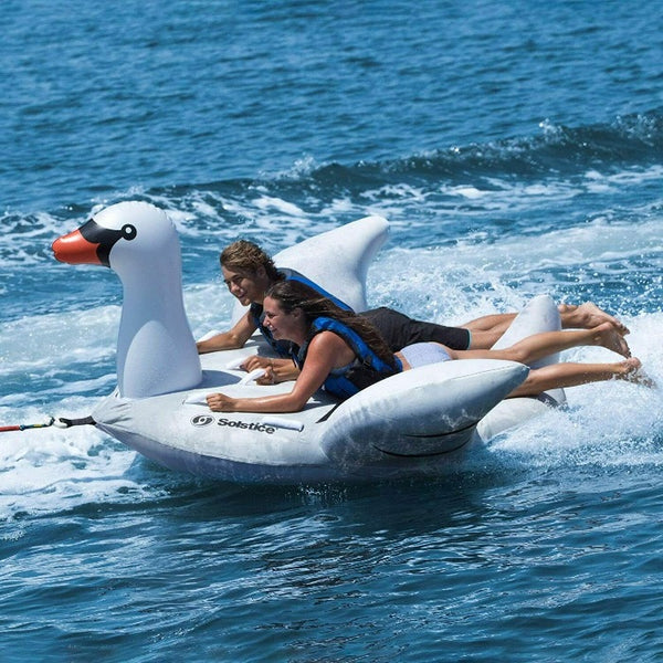 White inflatable swan float with a male and female riding it. They are both wearing life vests. They are both hanging on to multiple handle grips attached to the swan. Swan is being towed with two passengers.