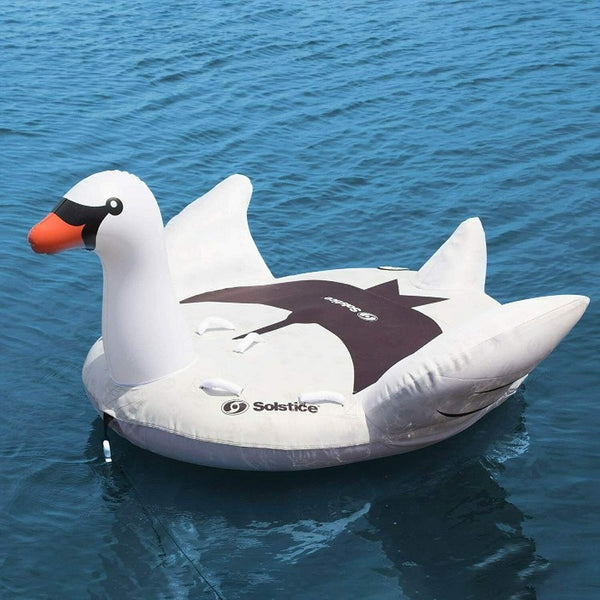 White inflatable swan floating on water. There is a rope attached to the front so it is ready to tow. Photo shows multiple handles. Swan head is facing to the left. There is black shading on the float platform in teh shape of a bird.