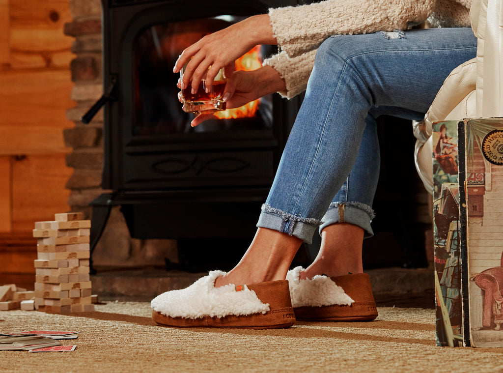 Acorn Moc II with collapsible heel on figure. Model wearing slippers while sipping whiskey by a fire