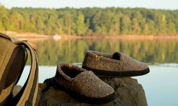 Men's Mocs in Earth Tex sitting on a rock next to a backpack overlooking a lake