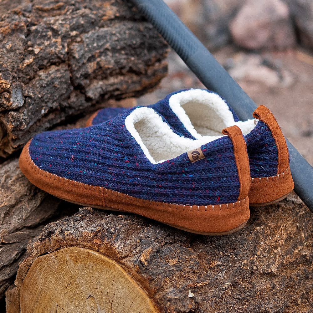 Camden mocs in Navy Blue sitting on a pile of wood
