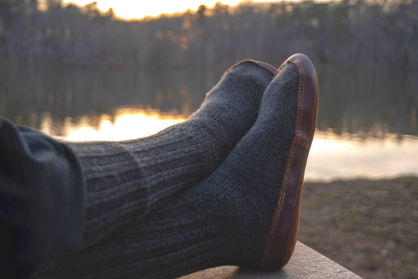 Acorn Slipper Sock on model relaxing on a deck sitting next to serene lake and pine trees