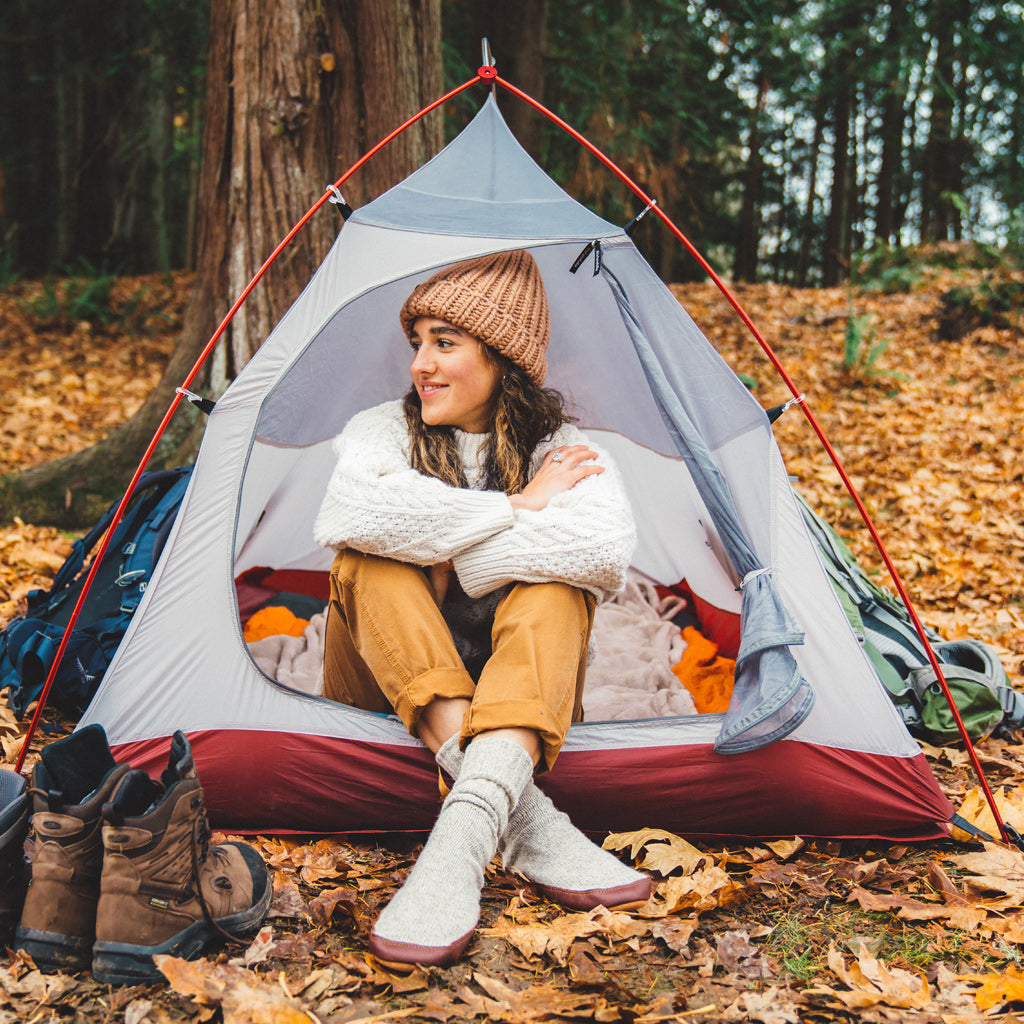 Female model sitting in a tent wearing her Grey Ragg Wool Slipper Socks